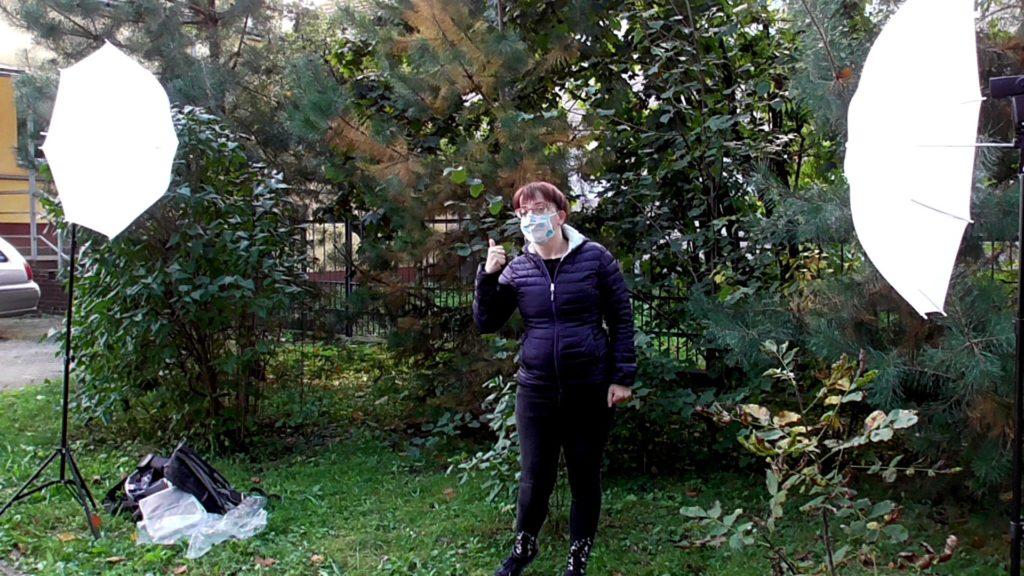 Justyna na tle zieleni i białych parasoli fotograficznych. Pokazuje gestem, że jest OK.