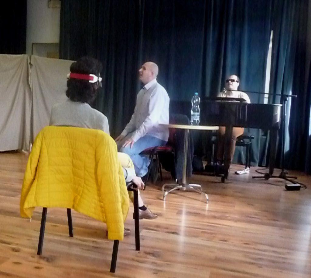 Łukasz Baruch udziela wskazówek, a akompaniuje mu Grzegorz Dowgiałło na fortepianie. Na pierwszym planie jeszcze Katarzyna Nowak.