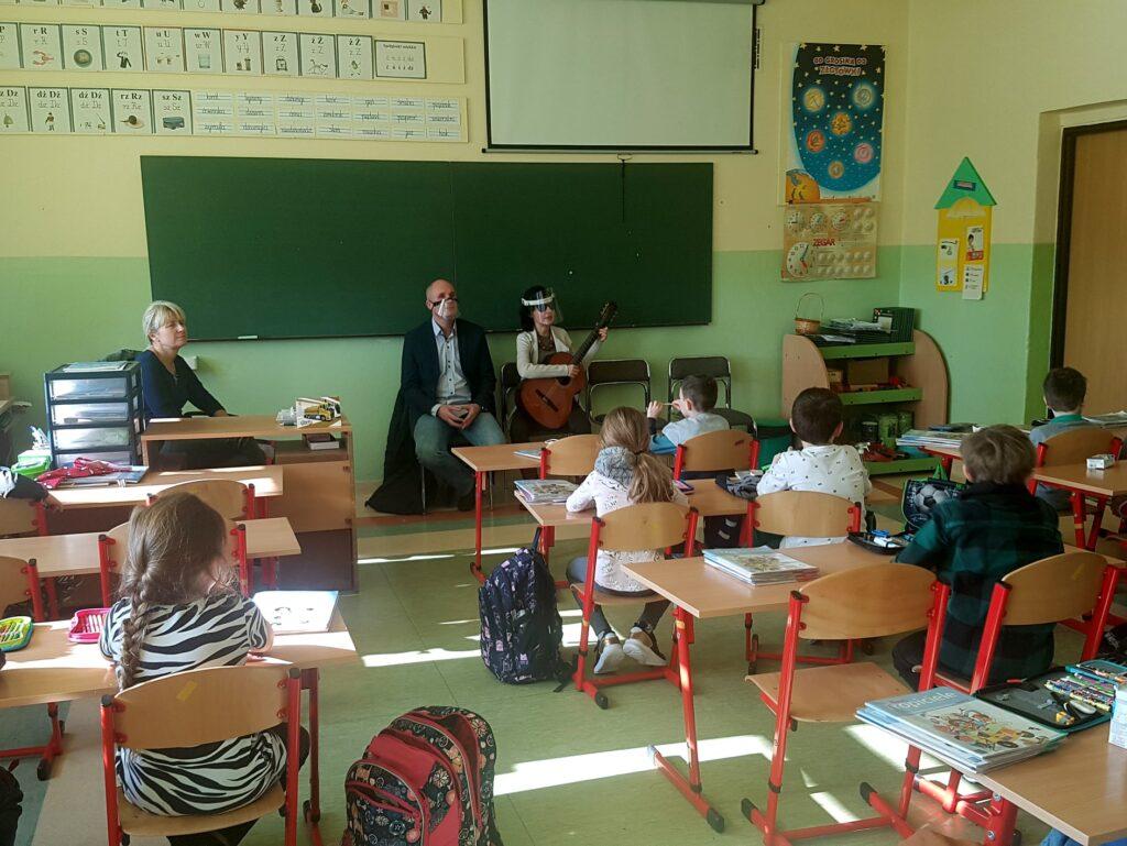Sala szkolna, zasłuchani uczniowie w ławkach, Katarzyna Nowak gra na gitarze. Obok niej Łukasz Baruch.