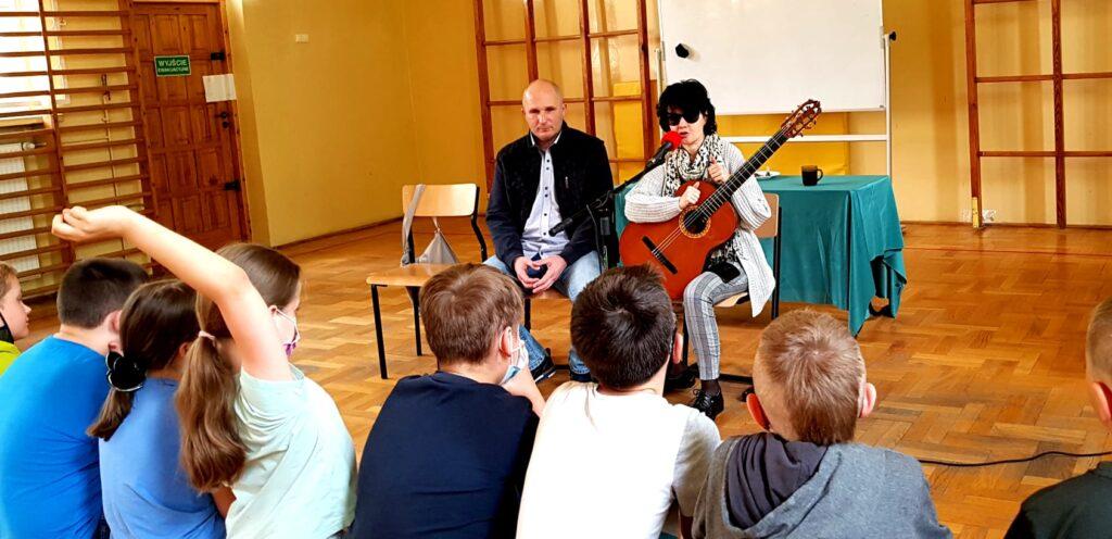 Kasia i Łukasz na spotkaniu z dziećmi. Jedno z dzieci podnosi rękę, aby zadać pytanie.