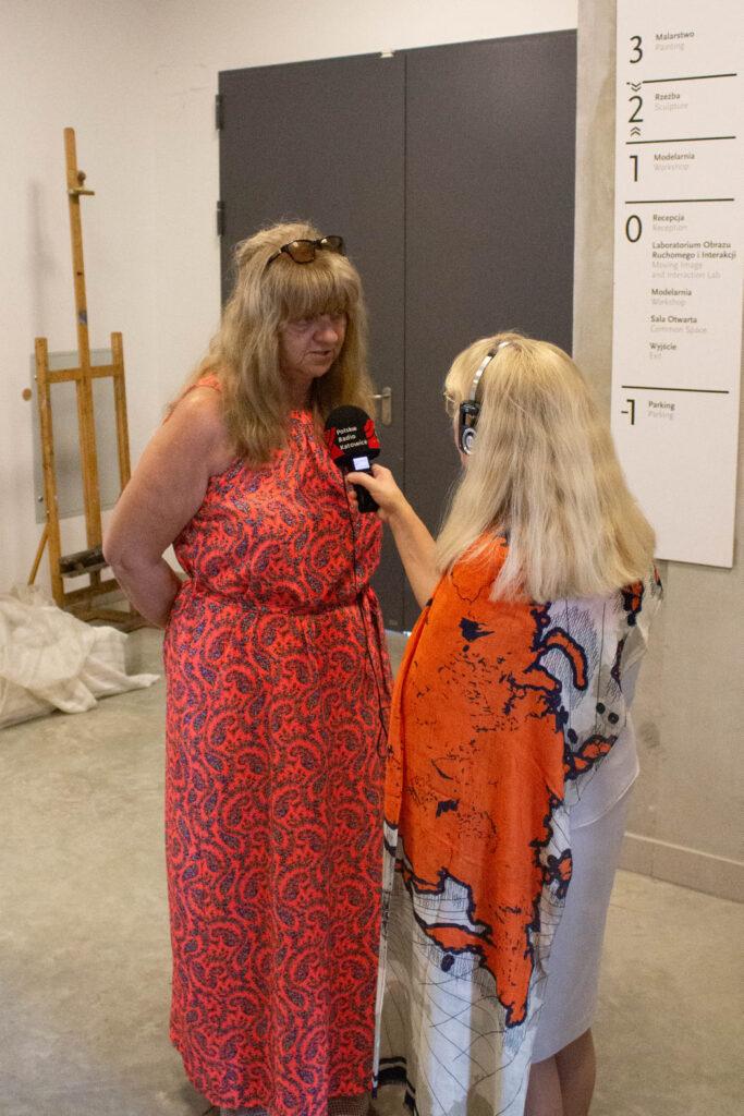 Pani Beata Tomanek prowadzi wywiad z Panią Ewą Pieczykolan, za nimi znajdują się drzwi do innej sali.