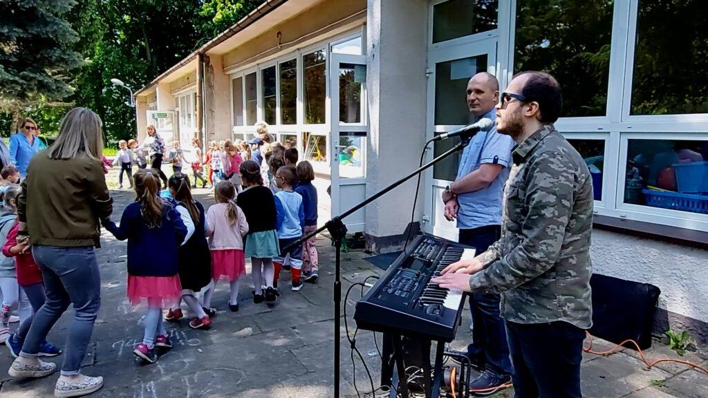 Grzegorz Dowgiałło gra na keyboardzie i śpiewa piosenkę o niedźwiedziu.  Towarzyszy mu Łukasz Baruch. Na drugim planie dzieci w kręgu wraz wychowawcami. Po środku koła skulony chłopiec czyli niedźwiedź.